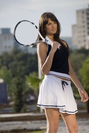 Young brunnete girl with tennis wear and equipment posing on the sun before game.
