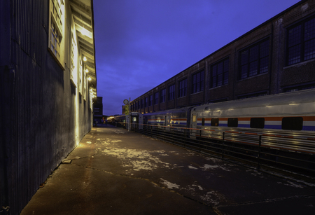 Old Railroad Building, Walkway And Train At Evening