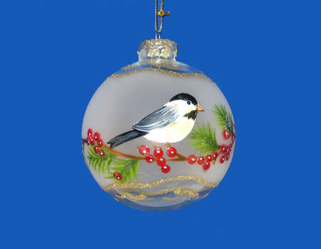 Hand-crafted Christmas tree ornament with picture of bird; blue background. Stock Photo