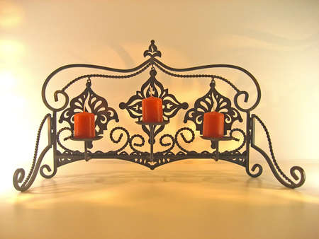 Fancy wrought iron candle holder with red votive candles. Imagens