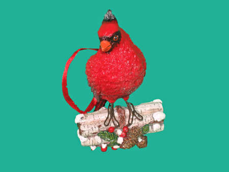 Red cardinal Christmas ornament on a turquoise background. photo