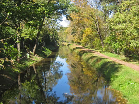 Canal in rural village in autumn with bicycle path. Stock Photo - 560425