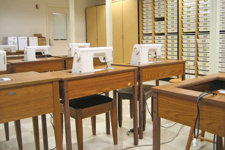 Sewing Classroom with Sewing Machines and Storage Cabinets.