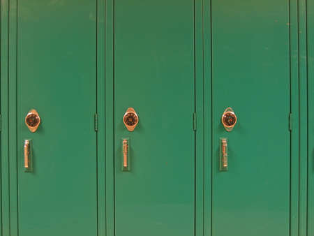 fairly: Three green school lockers with combination wheels; fairly close-up. Stock Photo