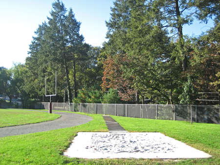 football goal post: School Track and Field in Autumn with Long Jump Path and Football Goal Post. Stock Photo