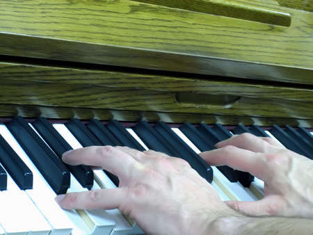 Two Hands Playing a Chords on a Piano Keyboard