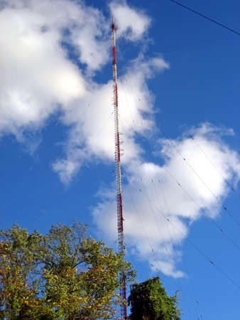 Tall ReceptionTransmitter Tower Against Blue Sky and White Clouds
