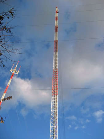 Two Tall Radio Towers Against A Partly Cloudy Sky