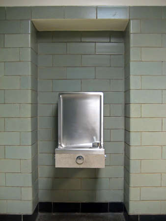 School Water Fountain Against Green Cinderblock Background