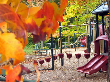 Playground in a park in October; colorful leaves.