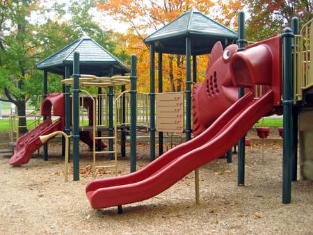 Playground in Autumn with Two Red Sliding Boards Imagens