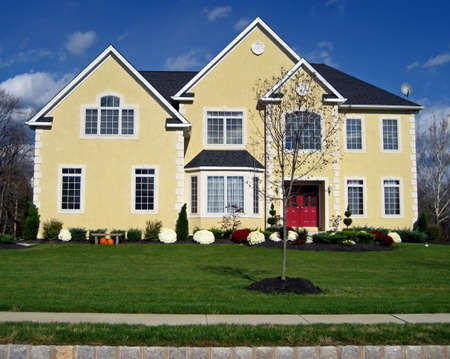 roomy: New, roomy executive style house with yellow facade and red door. Stock Photo