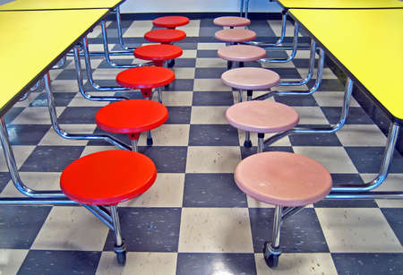 Pink and redorange school cafeteria seats and yellow cafeteria tables.