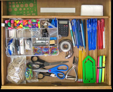 office cabinet: Open teachers desk drawer full of supplies.