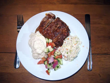 Plate of ribs, mashed potatoes, tomato cucumber salad, and coleslaw. Imagens