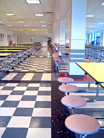 school cafeteria: Clean school cafeteria with many empty seats and tables.