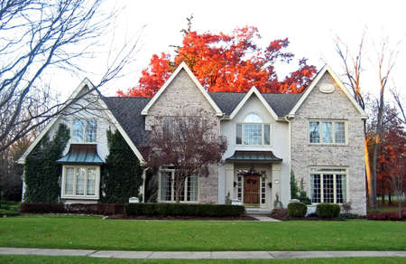 Elegant suburban house with brightly colored trees in autumn. Imagens