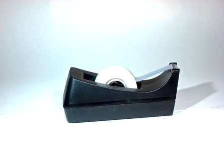 Black tape dispenser with a roll of scotch tape.