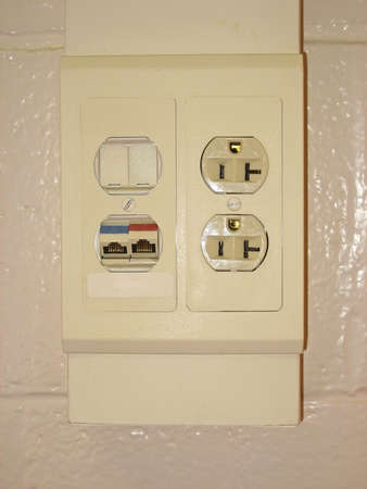 Ethernet port and electrical outlet on telow wall.