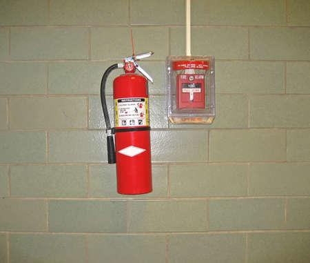 Fire Extinguisher and Emergency Alarm Against Cinderblock Background Imagens