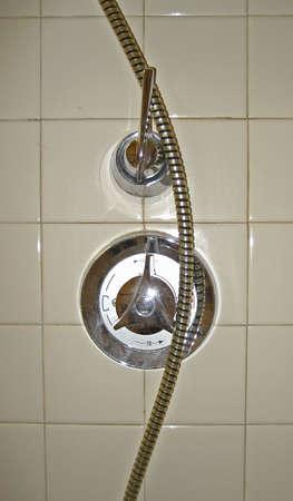 Two Shower Knobs Against Shiny Beige Tile Imagens