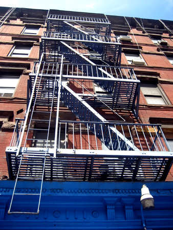 Fire escape and windows on a brick building facade in Manhattan, NYC