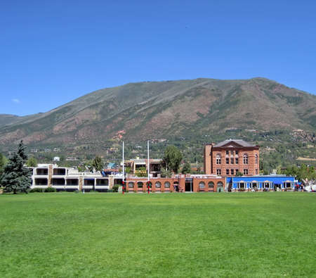 Field and Buildings in Aspen, Colorado with mountain in background.