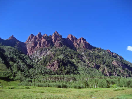 Jagged reddish-brown Rocky Mountain peaks in summertime.