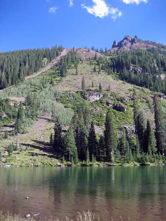 Lake in front of a steep mountain. Imagens