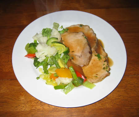 Pork loin slices with gravy and mixed steam vegetables.