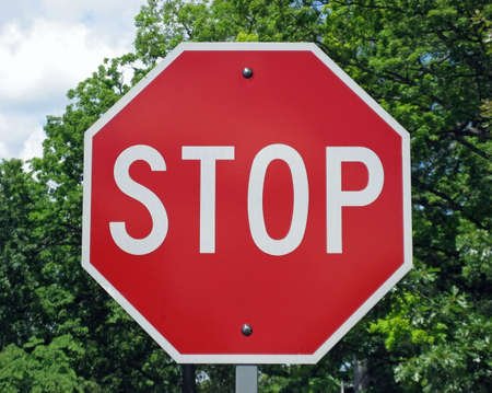 Stop sign with cloudy sky and trees in the background.
