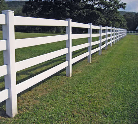 A long white fence on a mountain ranch.