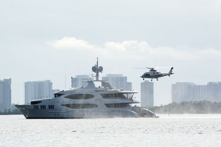 helicopter about to land on back of luxury motor yacht