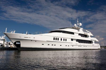 large white private mega yacht alongside dock