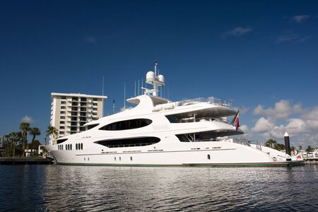 white mega yacht alongside dock with building in background photo