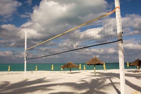 pelota de voley: beach volley ball net con sombrillas y mar turquesa
