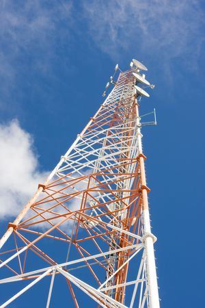 latticed: red and white latticed communications mast with blue sky background