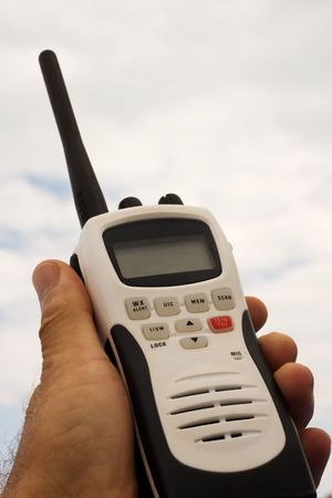 held: marine hand held radio against a sky background
