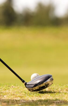 close up of driver golf club, and golf ball with reflection of golfer in club photo