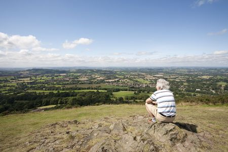man sitting on rocks looking at view of countryside photo
