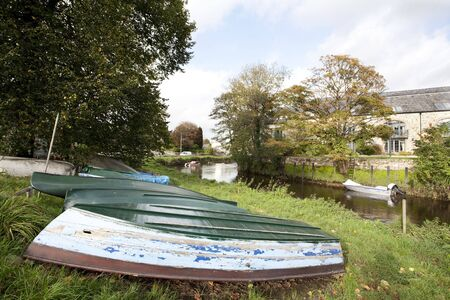 upturned: upturned boats on the grassy banks of a river Stock Photo