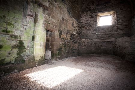 a rectangle of sunlight from a window in a dark castle room photo