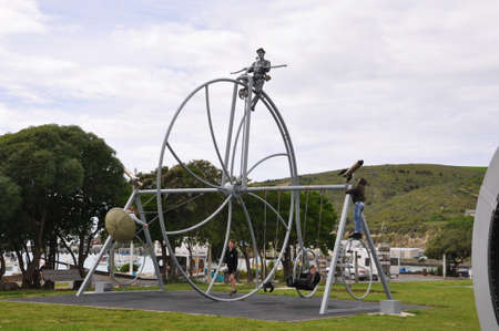 Oamaru, New Zealand, December 2, 2016: Giant Penny Farthing bicycle on a set of swings in the Steampunk park, in Oamaru, South Island, New Zealand.