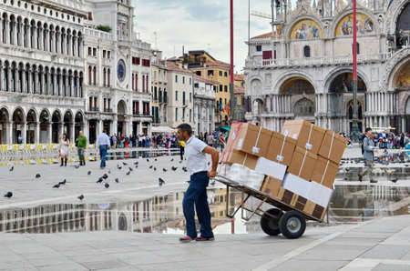 VENICE, ITALY - September 23, 2015: Unknown delivery person pulls a loaded cart through flooding in Piazza San Marco in Venice, Italy