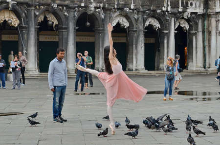 VENICE, ITALY - September 23, 2015: Unknown ballerina dances in flooded Piazza San Marco in Venice, Italy