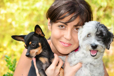 pincher: Young beautiful woman smiling and hugging her small black pincher dog and a white poodle
