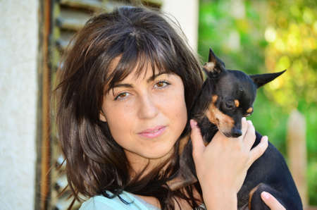 pincher: Young beautiful woman smiling and hugging her small black pincher dog