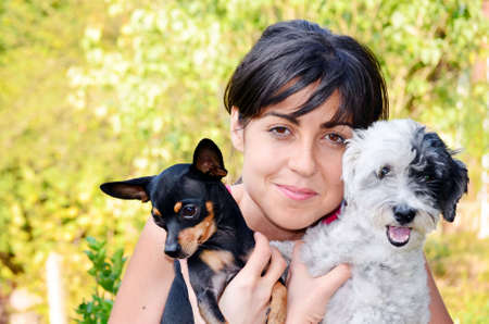 pincher: Young beautiful woman smiling and hugging a small black pincher and white poodle dog