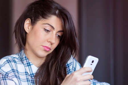 celos: Portrait of young sad annoyed woman, receiving bad sms