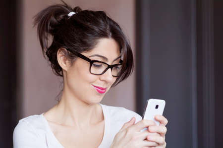 Portrait of young smiling woman receiving funny message Stock Photo